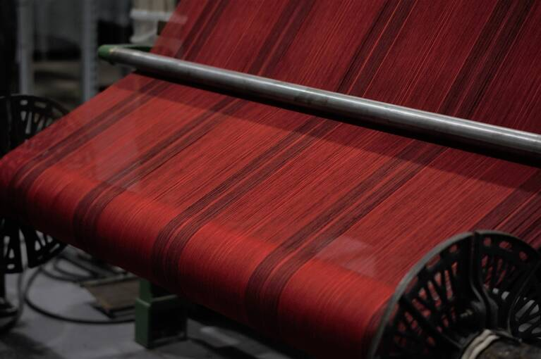 A red tartan being woven on a traditional loom.