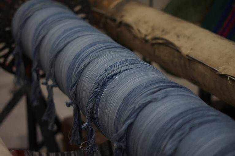 Blue woollen thread which will become a tartan textile on a loom.