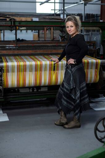 A woman stands in front of a traditional loom, which has a yellow and white tartan cloth being woven on it.