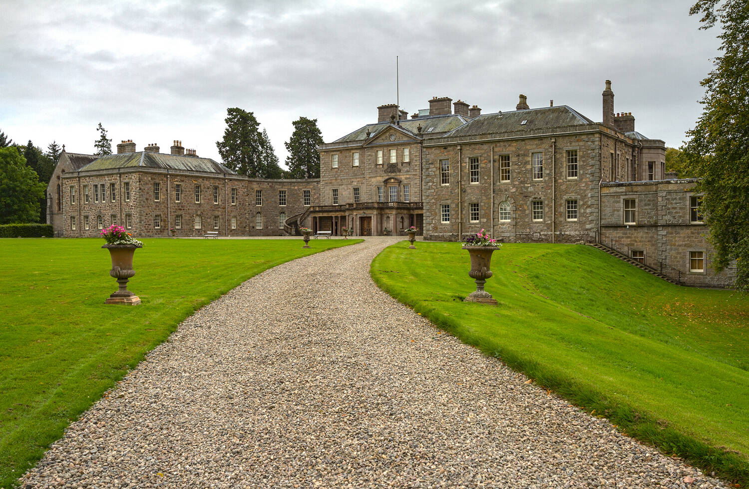 A gravel driveway leading to a grand Palladian mansion, Haddo House. Large stone urns with pink flowers in them stand either side of the driveway on immaculate green lawns.