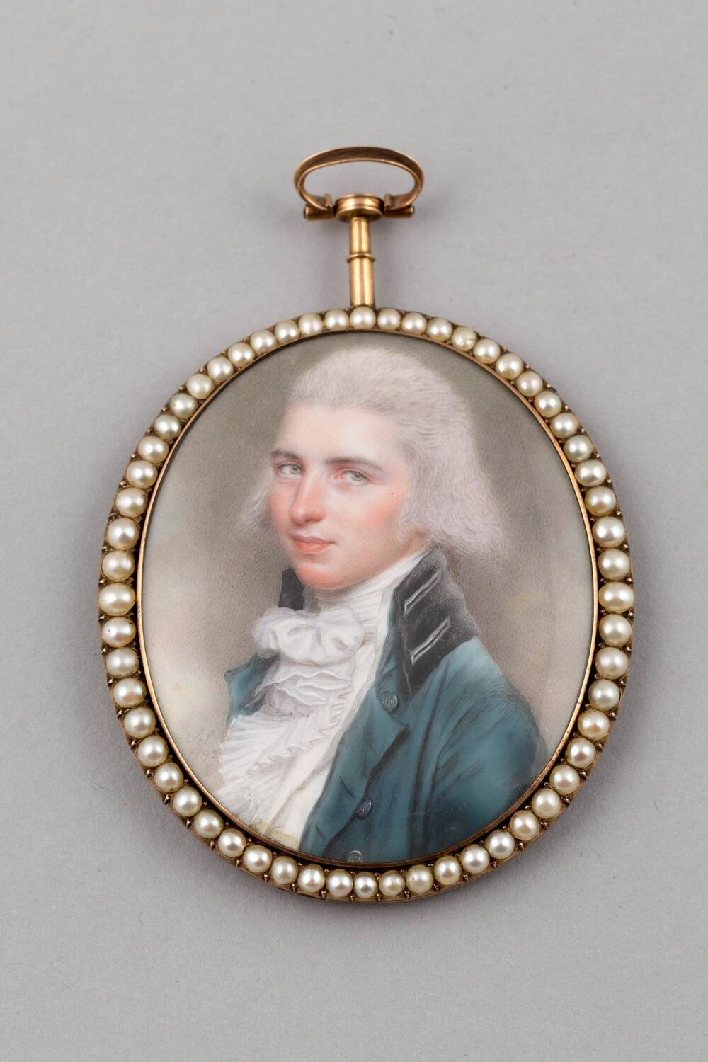 Miniature showing the head and shoulders of a man in a white powdered wig, wearing a blue jacket and a white shirt, with a large bow at the neck. The miniature is studded with pearls round the edge.