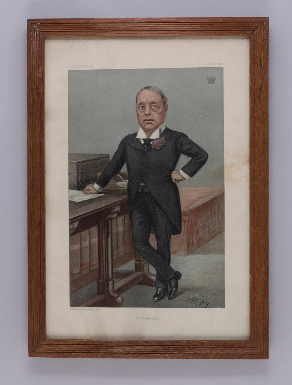 A coloured print in a wooden frame. It is of a man in a Victorian suit with a wing collar standing at a desk.