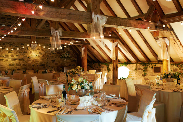 Inside a stone barn with wooden rafters, strung with fairy lights. Round tables have been set up for a wedding reception.
