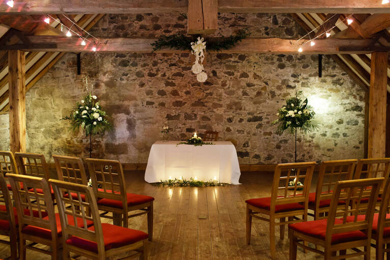 A stone barn with wooden rafters and atmospheric lighting, set up for a wedding ceremony
