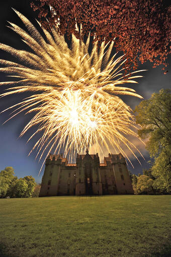 A fireworks display over Fyvie Castle at night