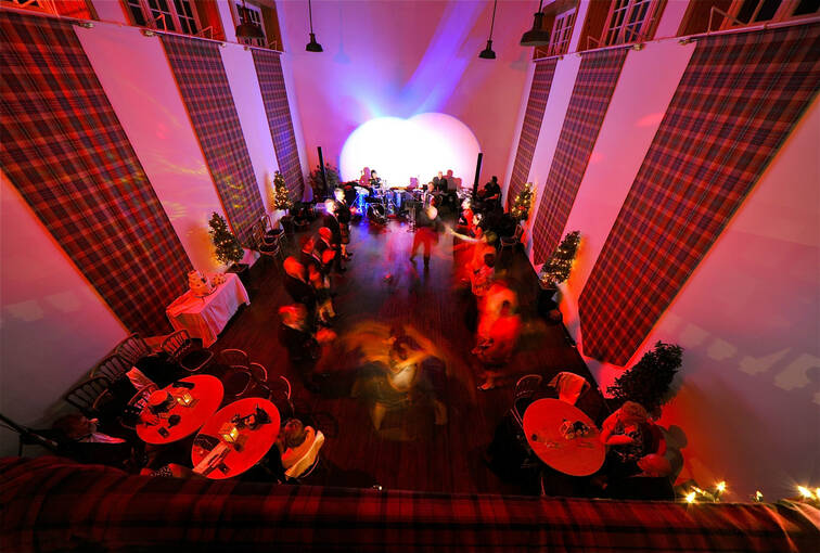People dancing at a wedding reception in a room lined with tartan hangings and lit in an atmospheric pink/red tone.