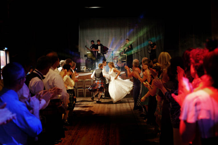 A bride and groom dancing at the end of a room, with wedding guests looking on.