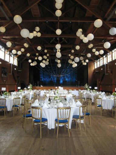 A high-ceilinged hall set up for a wedding reception.