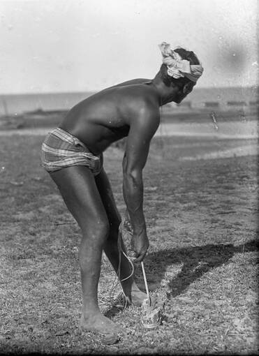 A black and white photo of a Sri Lankan man working in a field.