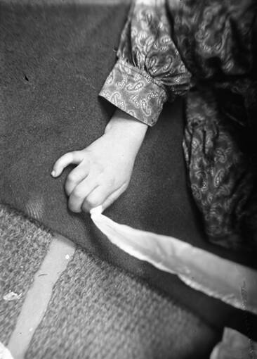 A black and white photo of a close up of a girl's hand. She holds a pale piece of cloth between her forefinger and thumb.
