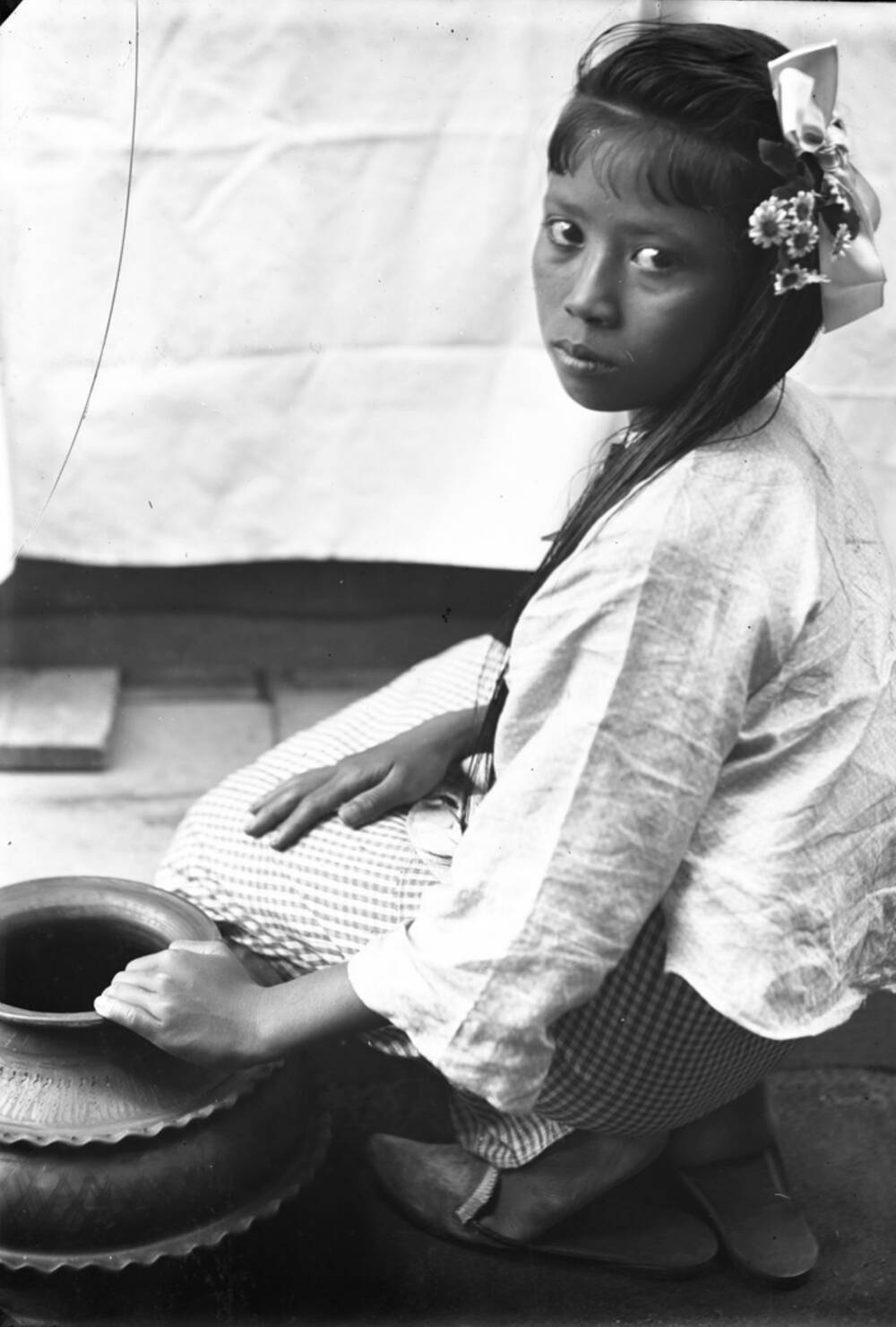 A black and white photo of a Sri Lankan girl kneeling in an interior. She rests her left hand on a ceramic jug beside her.