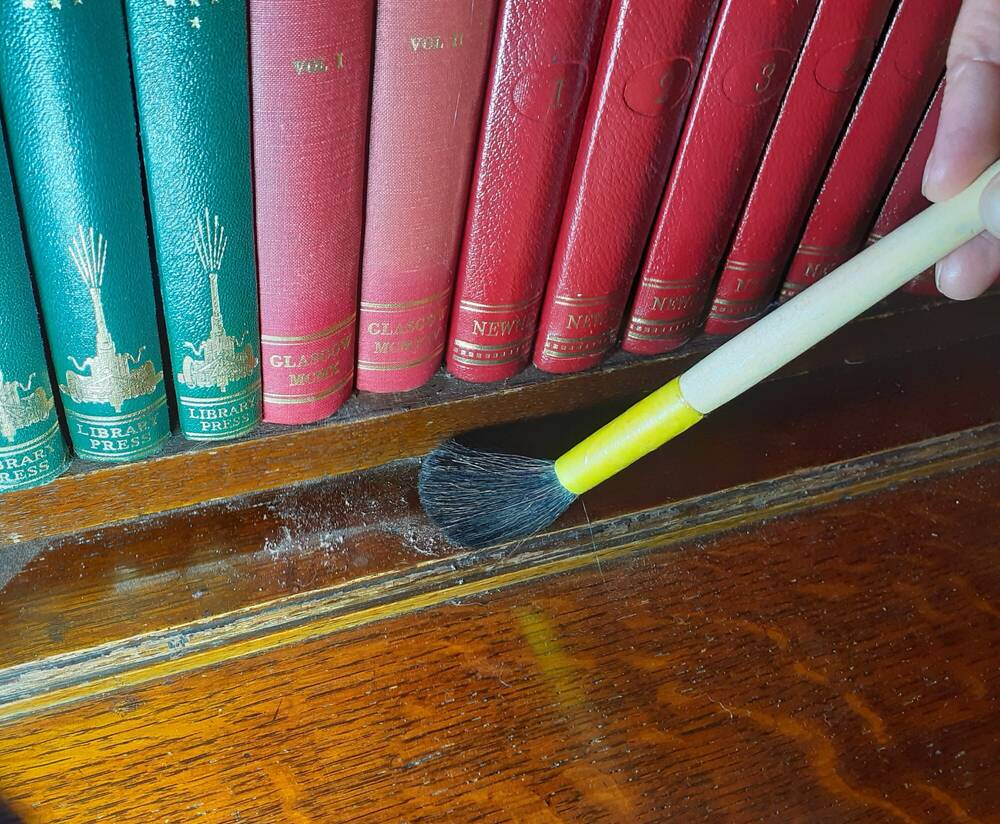 Close-up of a bookcase being dusted with a paintbrush.