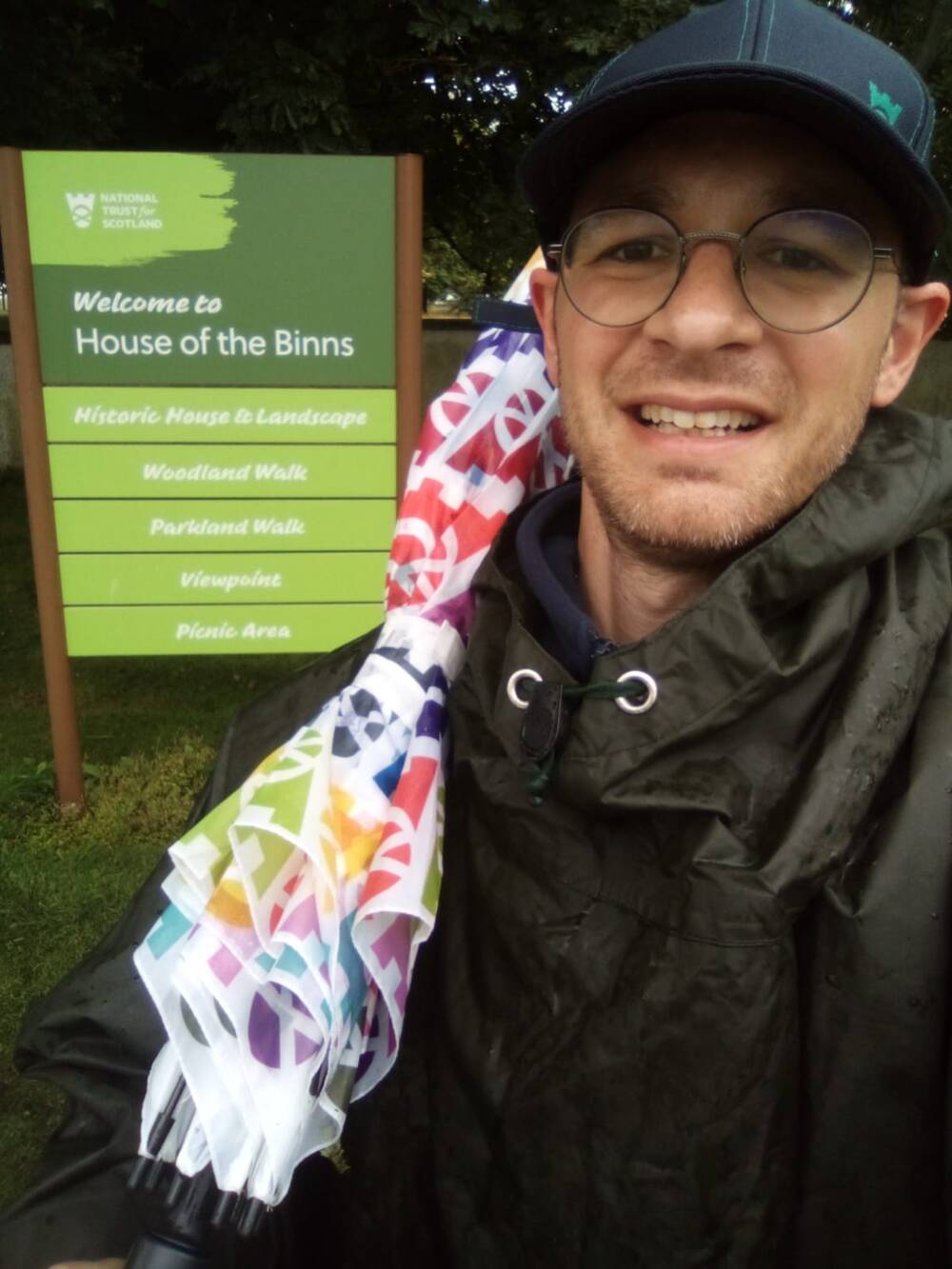A man is holding a National Trust for Scotland umbrella at the House of the Binns.