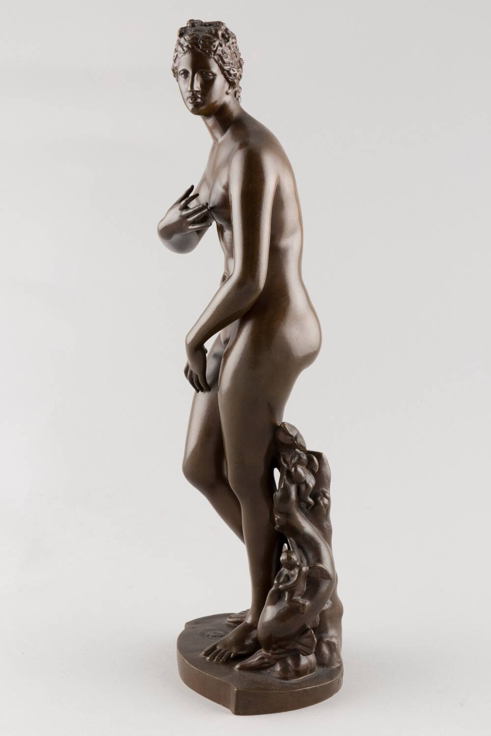 Side view of a bronze statue of Venus, with her right hand covering her left breast and her left hand on her right thigh.