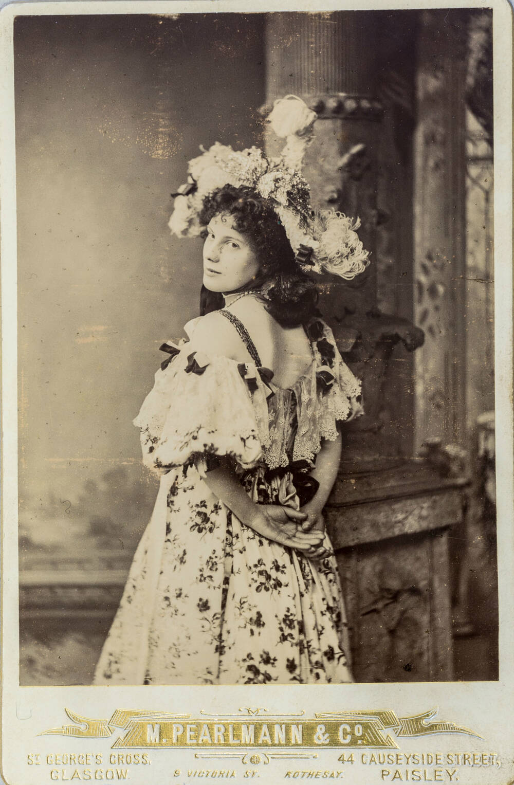 A black and white photo of a woman wearing a flowery hat and dress with her hands behind her back, looking over her shoulder.