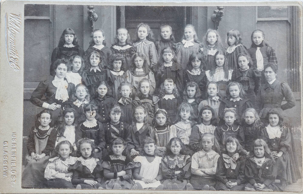 A black and white photo of 44 school children and two teachers variously sitting and standing in 5 rows.