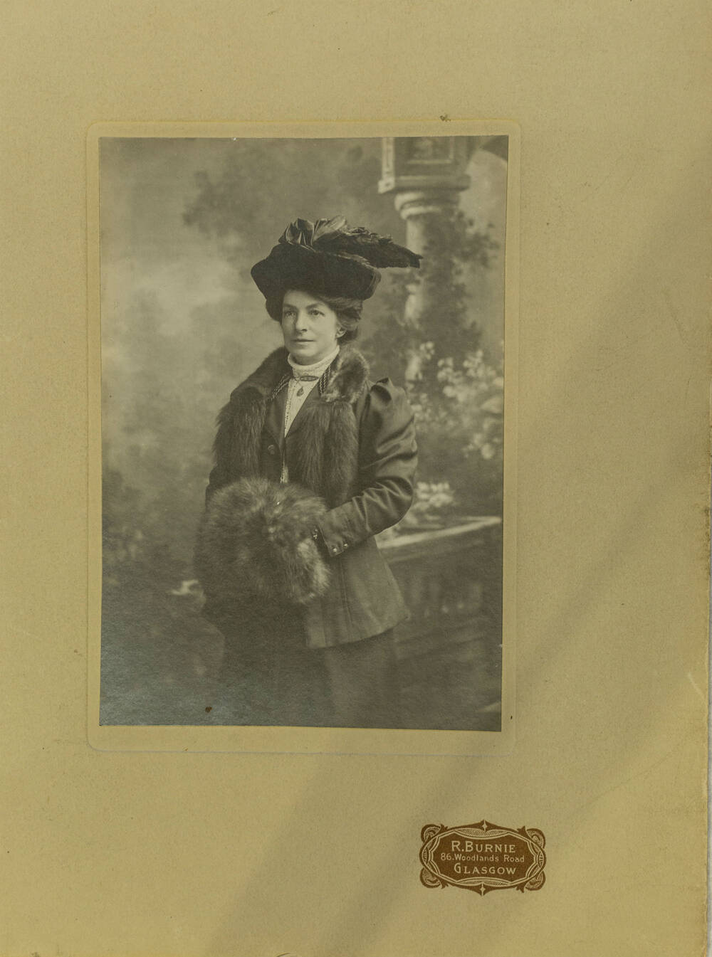 A black and white photo of a woman wearing a large hat, an animal fur around her neck and holding a fur muff.