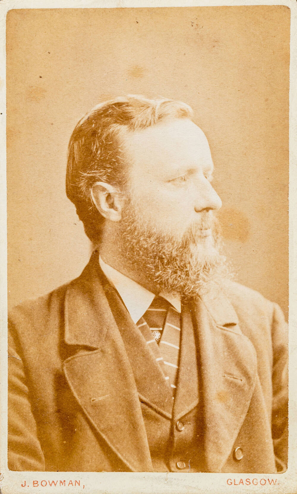 A black and white photo of the head and shoulders of a bearded man wearing a suit and tie, looking to his left.
