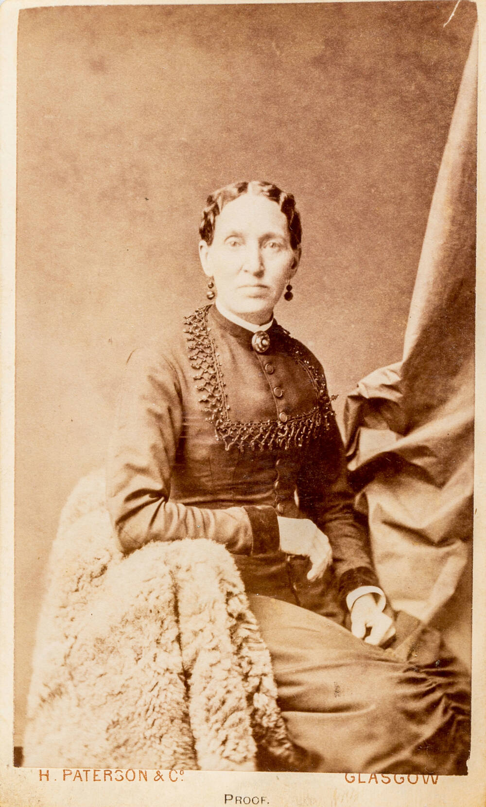 A black and white photo of a woman sitting on a fleece-covered chair. She wears a dark dress with beaded decoration.