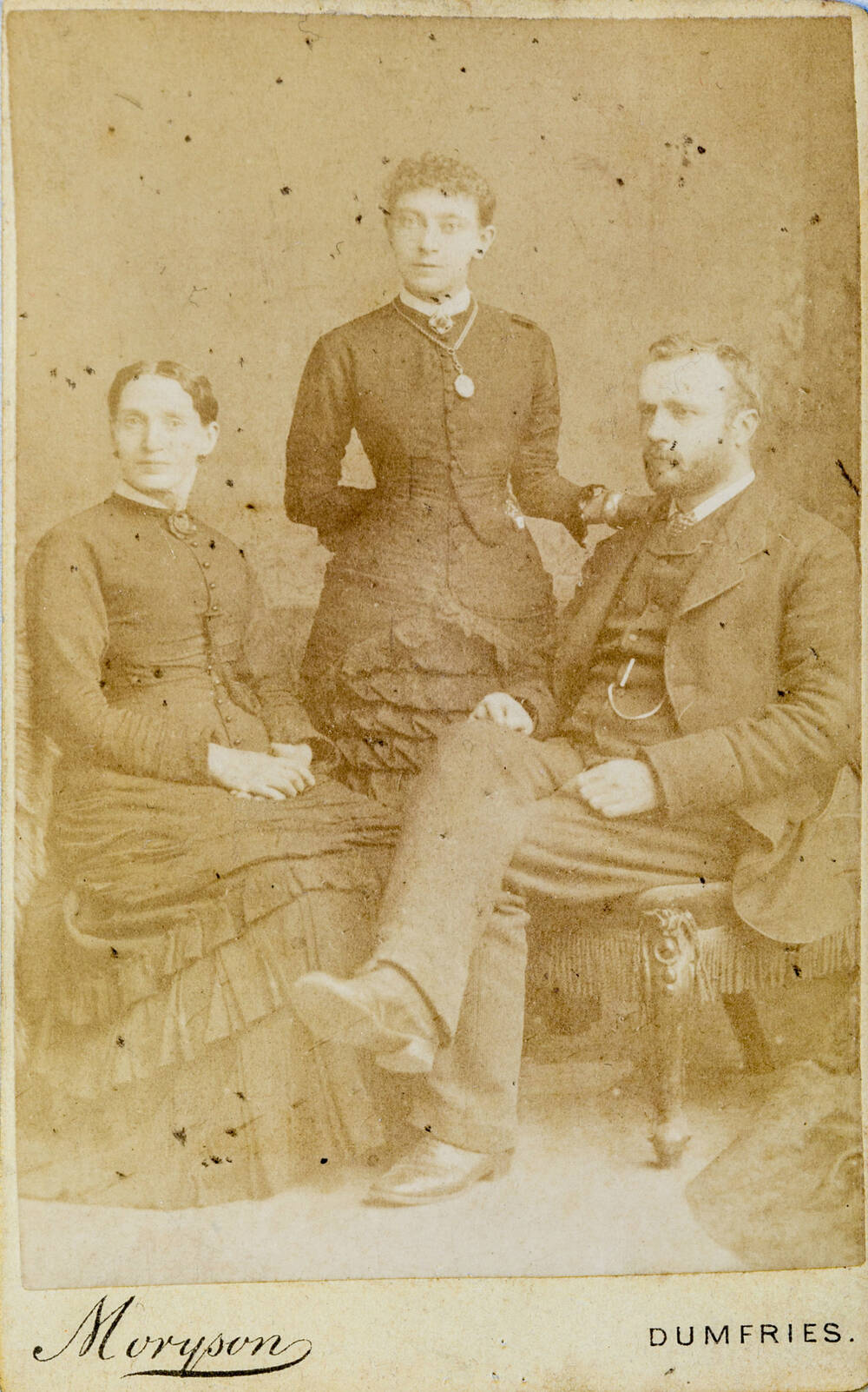 A black and white photo of a woman and man sitting down with a woman standing between them. They are wearing dark clothes.