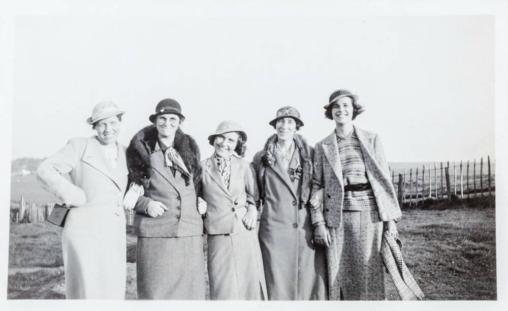 A black and white photo of five women wearing hats and 1930s fashion on a golf course. They are smiling and have linked arms.