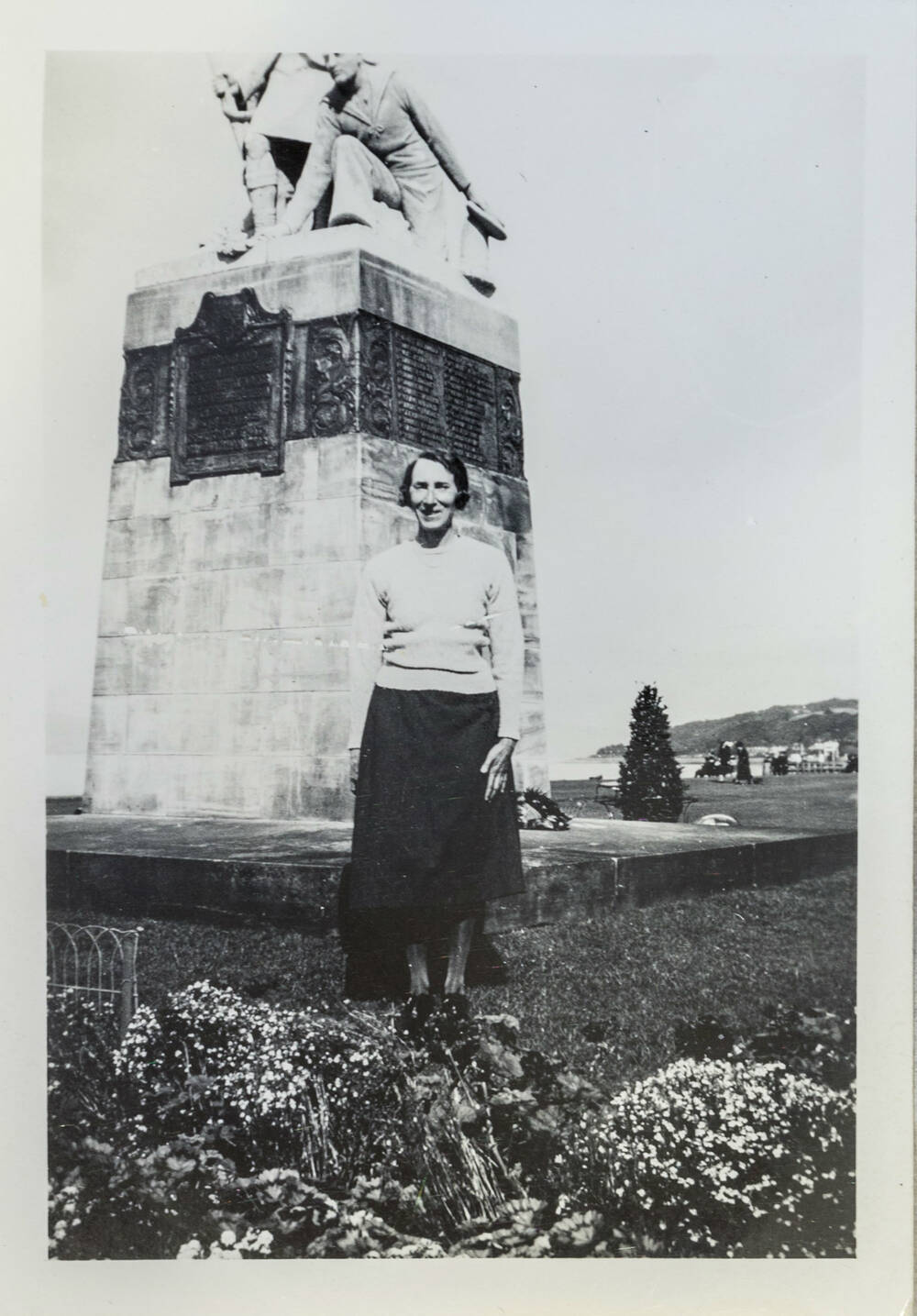 A black and white photo of a woman standing in front of a war memorial comprised of a square stone base with figures on top.