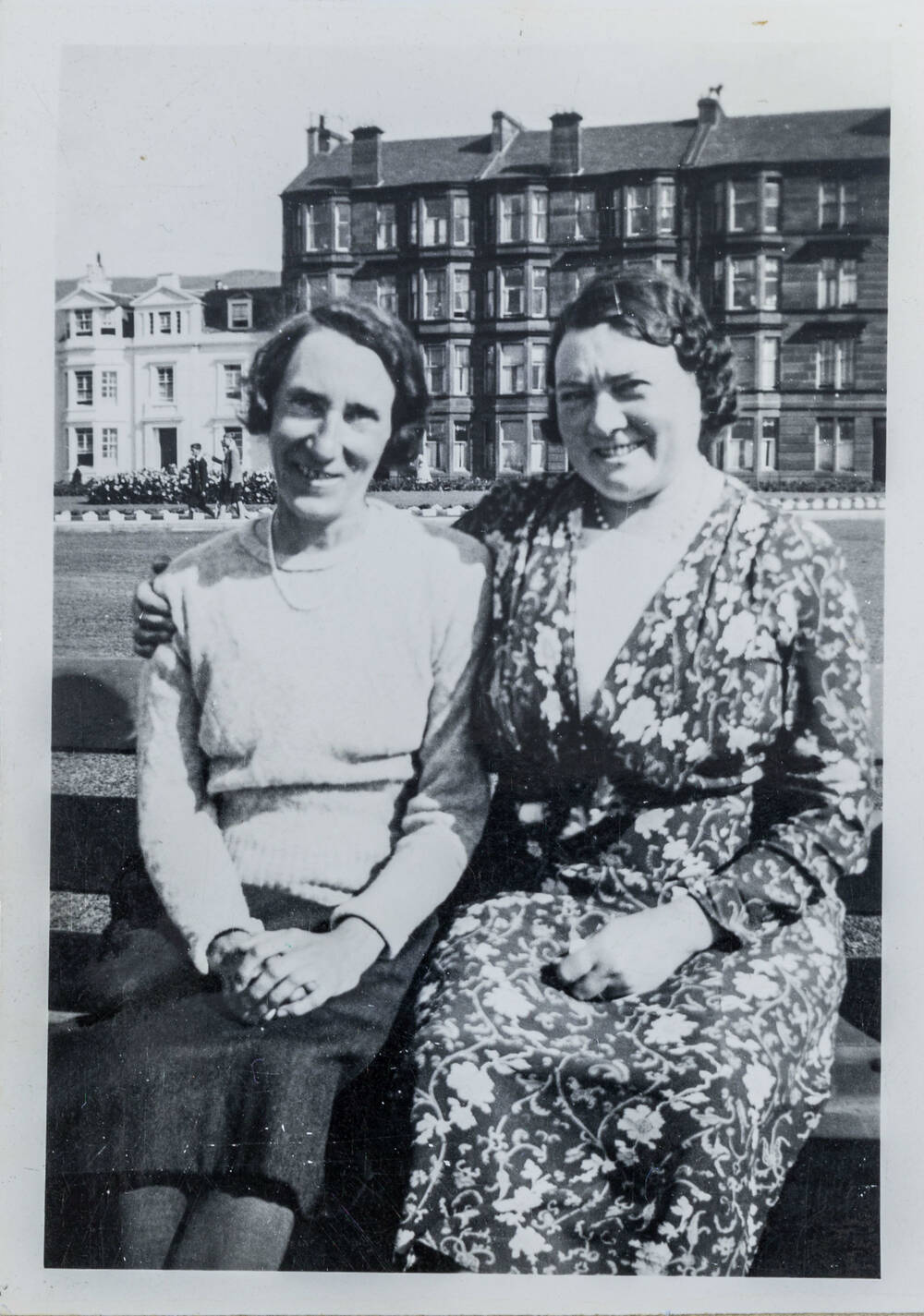 A black and white photo of two women sitting on a bench and smiling. The woman on the right has her arm around the other.