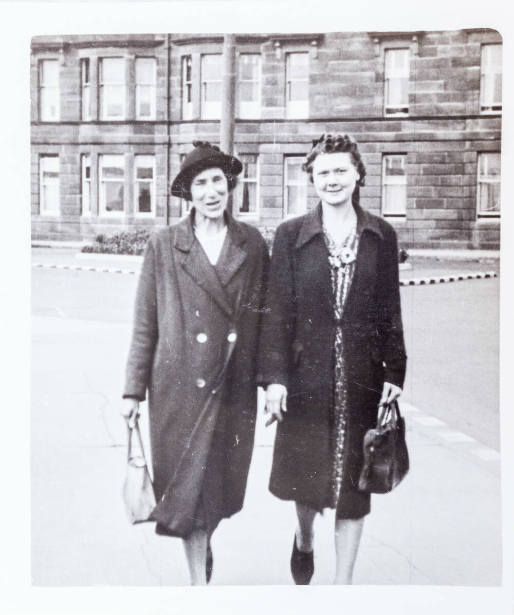 A black and white photo of two women walking along a street. They carry handbags and the woman on the left wears a hat.