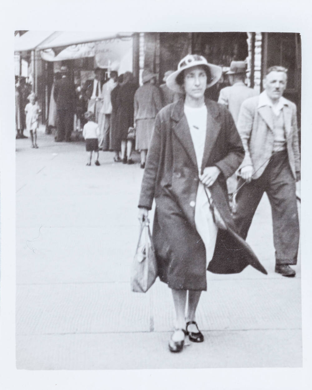 A black and white photo of a woman walking along a street wearing a hat and coat and carrying a handbag in her right hand.