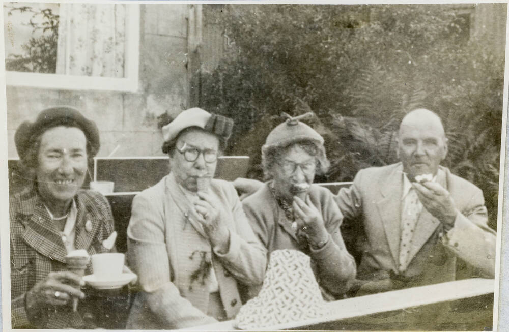 A black and white photo of three women and a man eating ice cream. The man sits on the right, the woman on the left holds a cup.