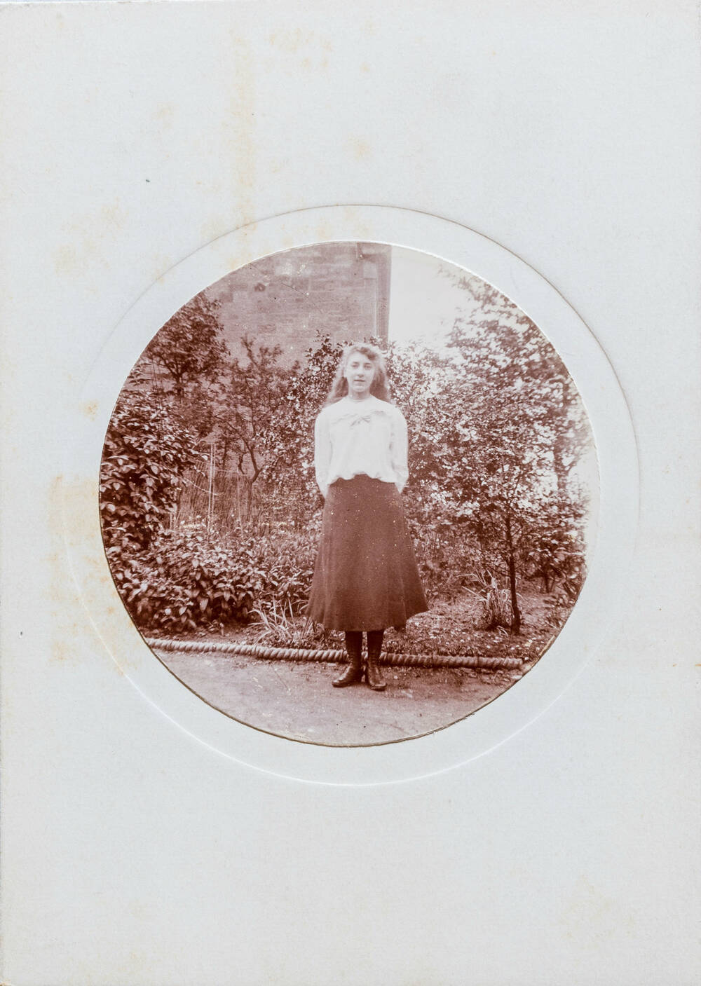 A circular black and white photo of the same young woman wearing the same white top and dark skirt standing in the same park.