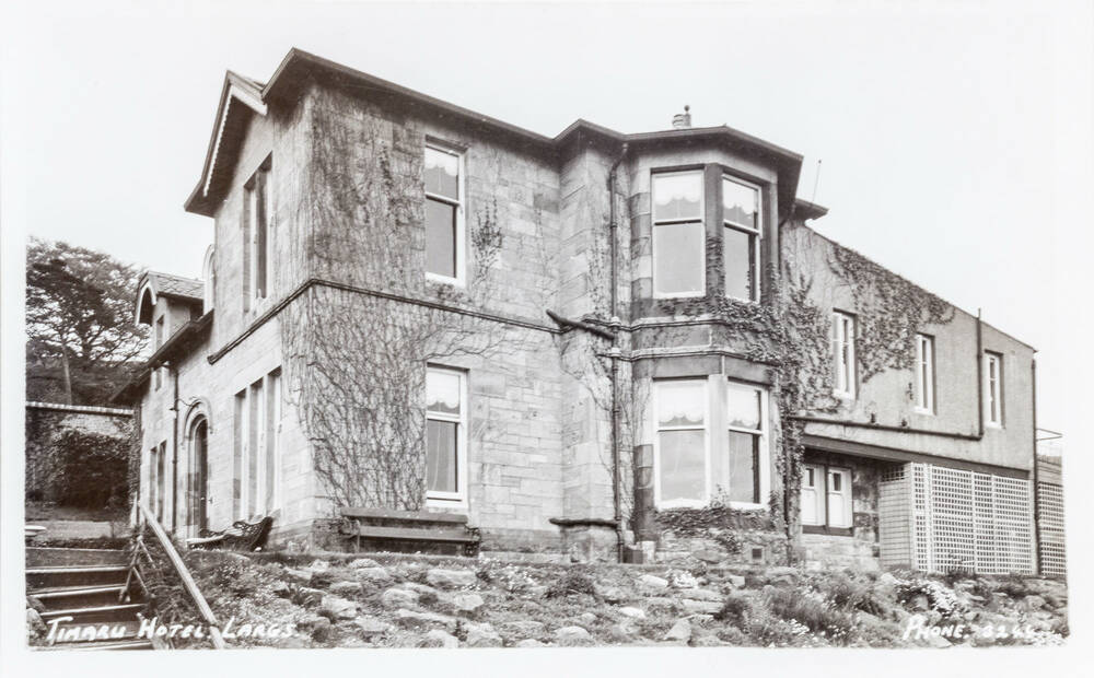 A black and white postcard of a stone building with bay windows and steps leading up to it captioned 'Timaru Hotel, Largs'.