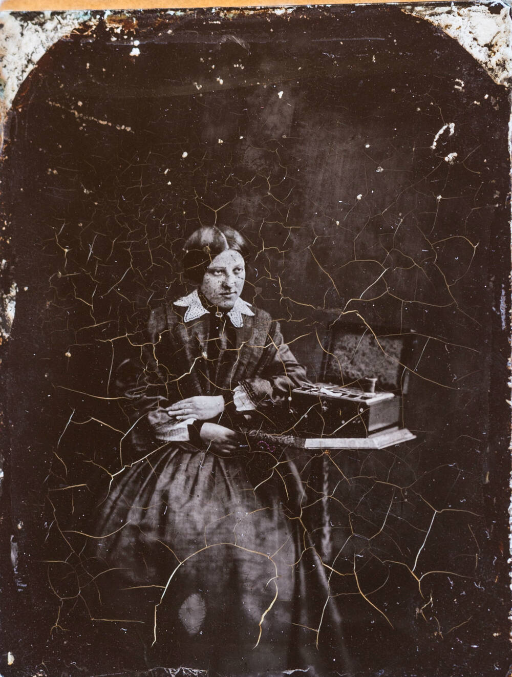 A black and white photo of a young woman in a black dress and lace collar sitting by a table. The photo is cracked.