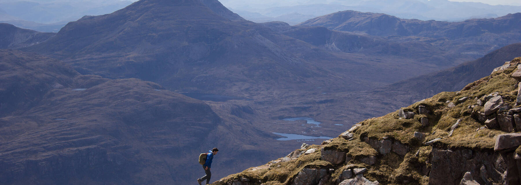 A young man hiking a knife-edged mountain ridge on the Liathach Ridge