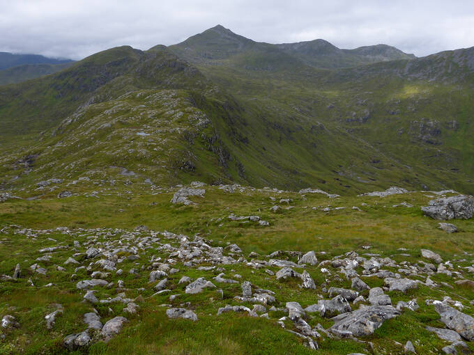 Mountain peaks in summer at West Affric. Taken from An Socach, the view looks towards another pointed peak. A grassy area with rocky outcrops is in the foreground.