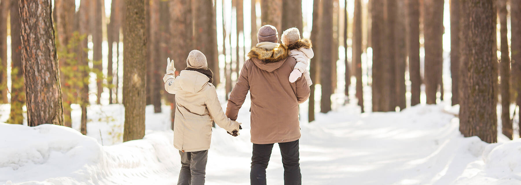 A family walks in snowy woods