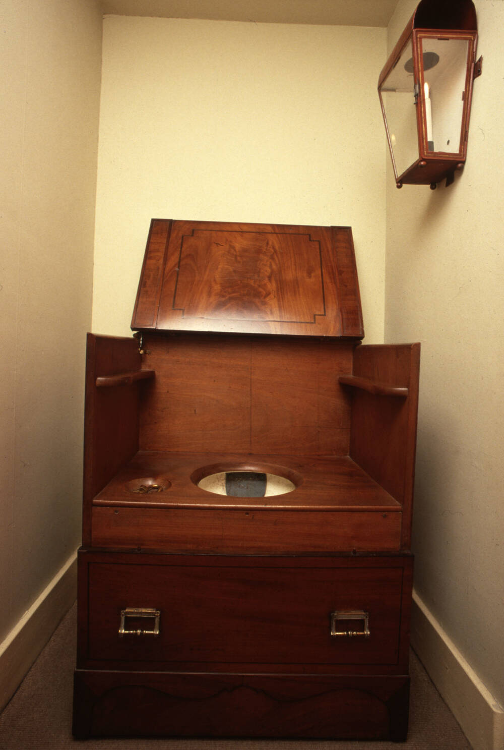 wooden commode in a very narrow room